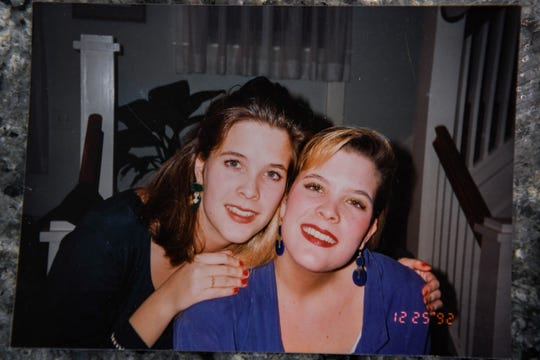 "Jenny Carrieri shows a photo with her identical twin sister, Jody LeCornu, who was killed in Baltimore 23 years ago. Carrieri is working to spread the story of the unsolved murder. ""I just become so consumed with it,"" she said on Monday, March 25, 2019."