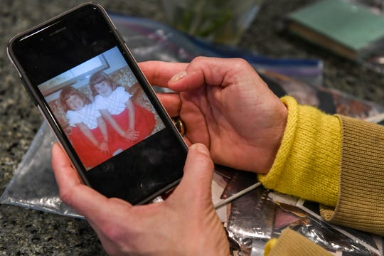 "Jenny Carrieri shows a photo with her identical twin sister, Jody LeCornu, who was killed in Baltimore 23 years ago. Carrieri is working to spread the story of the unsolved murder. ""I feel like I'm so close,"" she said on Monday, March 25, 2019."