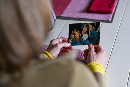 "Jenny Carrieri looks at an old family photo in her Easton home on Monday, March 25, 2019. Carrieri is working to spread the story of the unsolved murder of her twin sister, Jody LeCornu, who was killed 23 years ago. ""I'm always moving— it's like I can't sit still and I'm unsettled,"" she said."