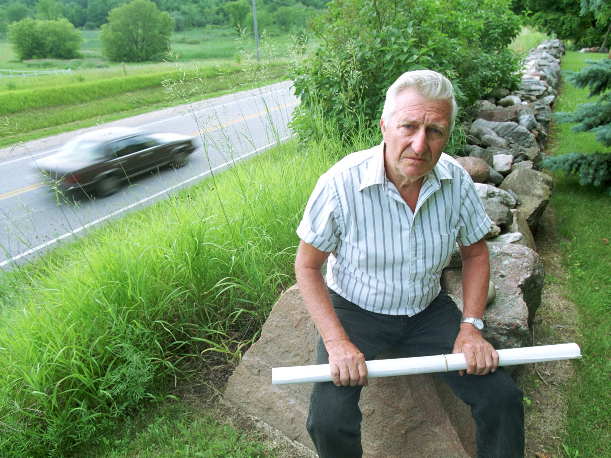 in 2001 recallled David Steffes the years of memories from times spent on his homestead property with his family on County Highway C near the intersection of Highway 23 just west of Plymouth. Memories such as the stone fence built over a summer by his son with rocks and boulders collected in nearby fields. The plan held in Steffes' hands lays out the state's plan to demolish his home, barns, the many trees planted as seedlings and of course the stone fence, to make room for the four lane expansion of Highway 23 and revamping of the Highway C intersection.  Press photo by Jeffrey Machtig