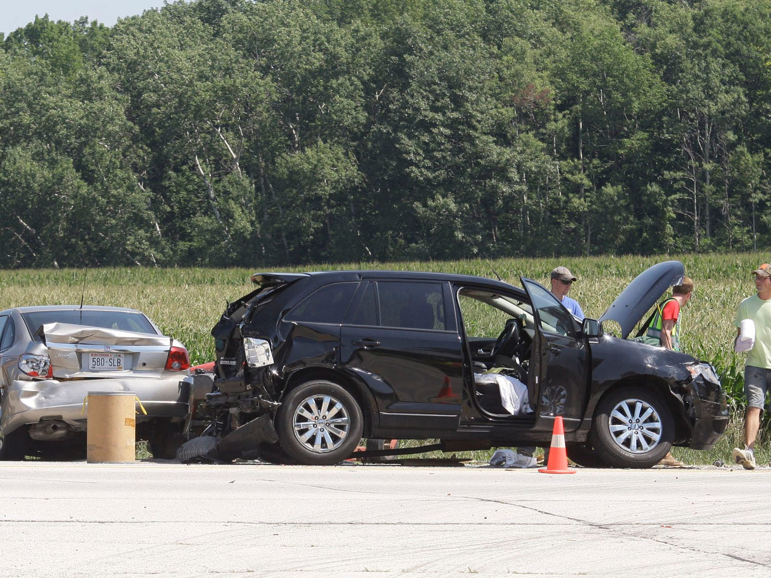 Rescue workers investigate at three-vehicle crash Wednesday August 3, 2011 at state Highway 23 and Plank Road.