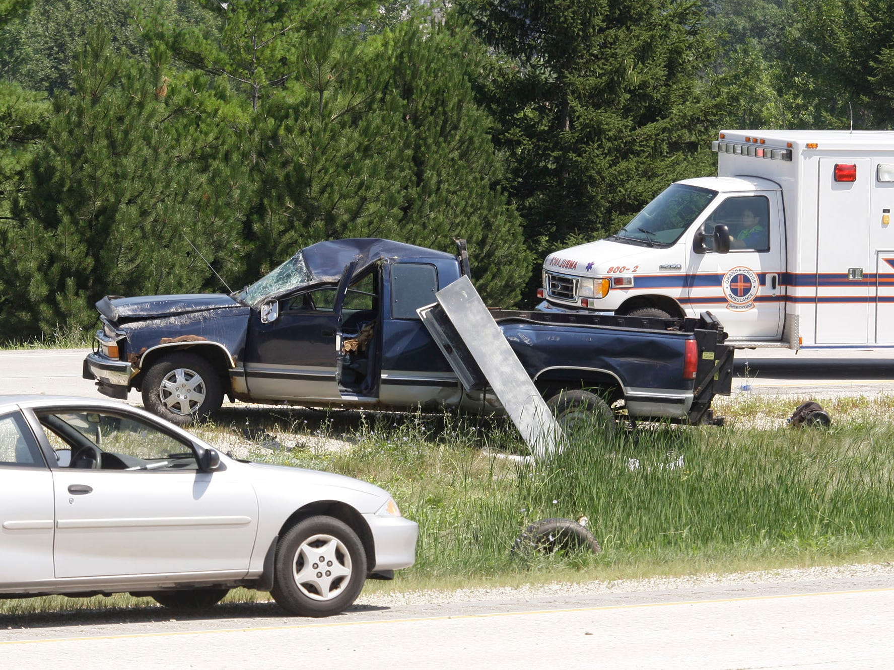 An Orange Cross ambulance conveys the driver of a rollover crash, Wednesday, August 3, 2011, at state Highway 23 and Sunset Road near Plymouth, Wis..