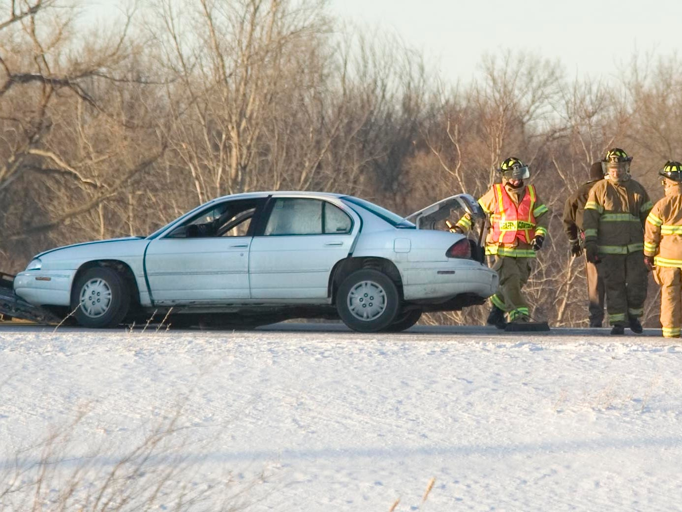 Firefighters gather around a damaged car along state Highway 23 at County U Friday January 16, 2009.  Officials closed a section of state Highway 23 to take care of the crash