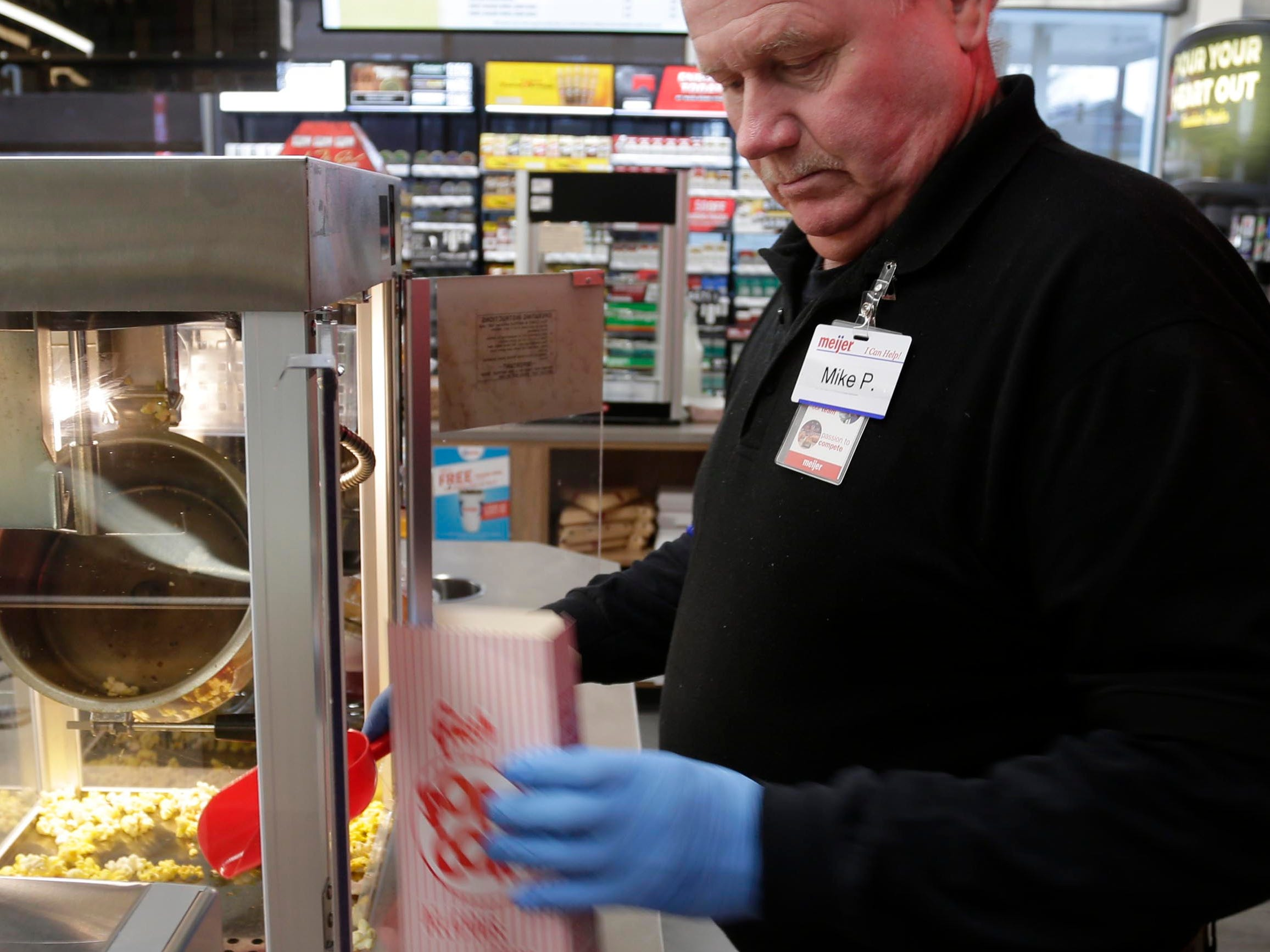 Meijer employee Mike Pellowski boxes up pop corn at the new Meijer gas station, Thursday, March 28, 2019, in Sheboygan, Wis.