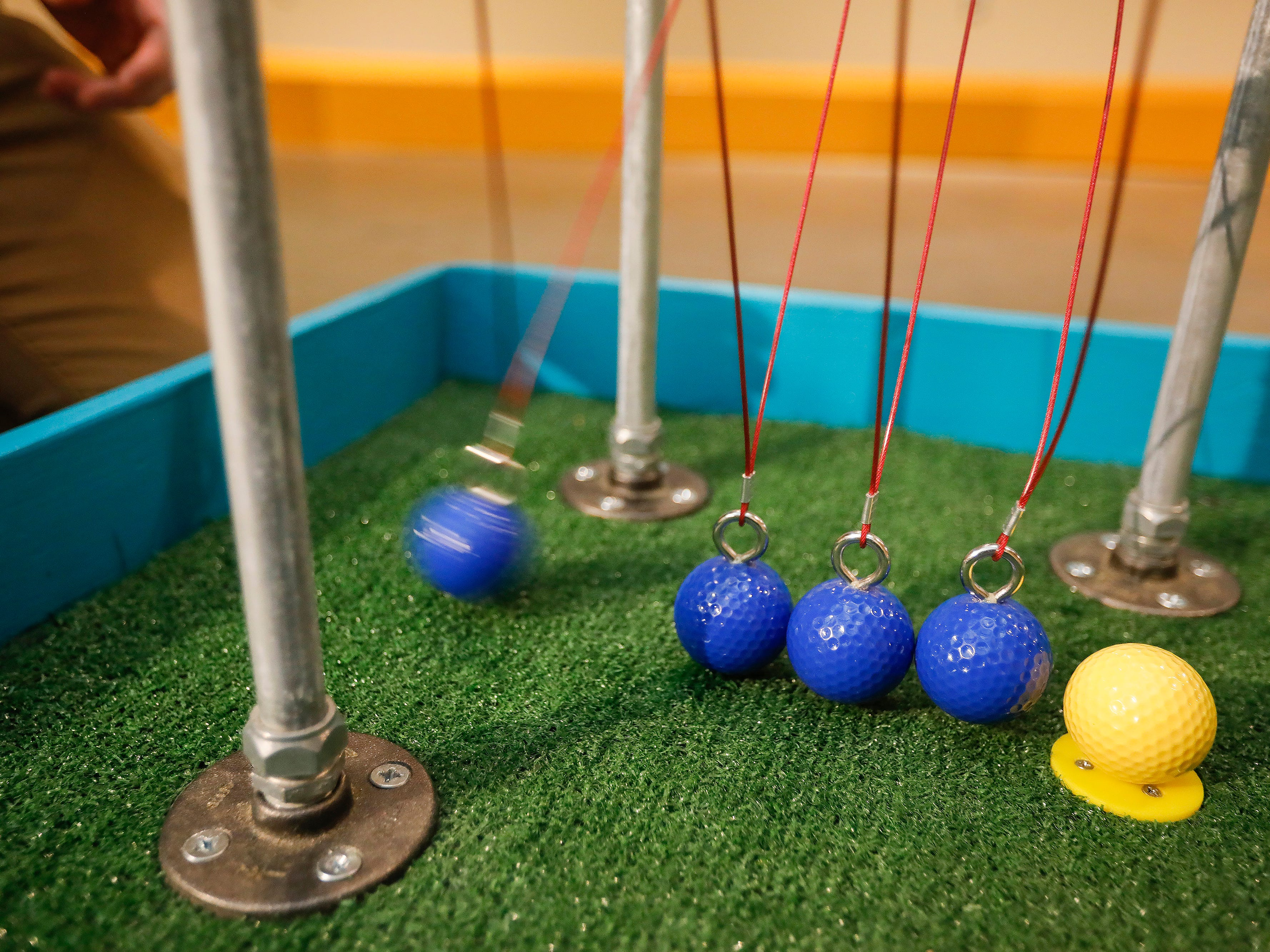 Rob Blevins, executive director at the Discovery Center, uses a Newton's cradle to take his shot at the new 9-hole indoor miniature golf course at the science museum. The new exhibit opens to the public on Sunday, March 31, 2019.