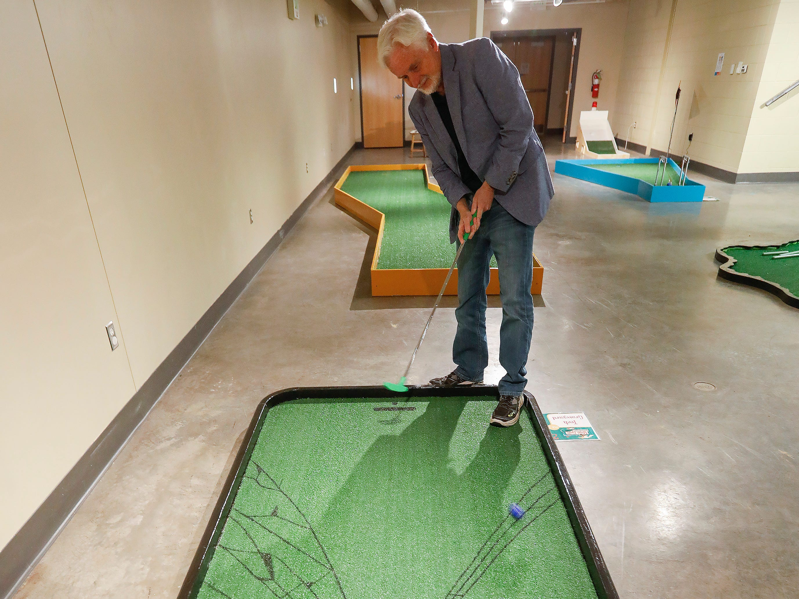 Steve Pokin takes a shot on the second hole of the new 9-hole indoor miniature golf course at the science museum. The new exhibit opens to the public on Sunday, March 31, 2019.