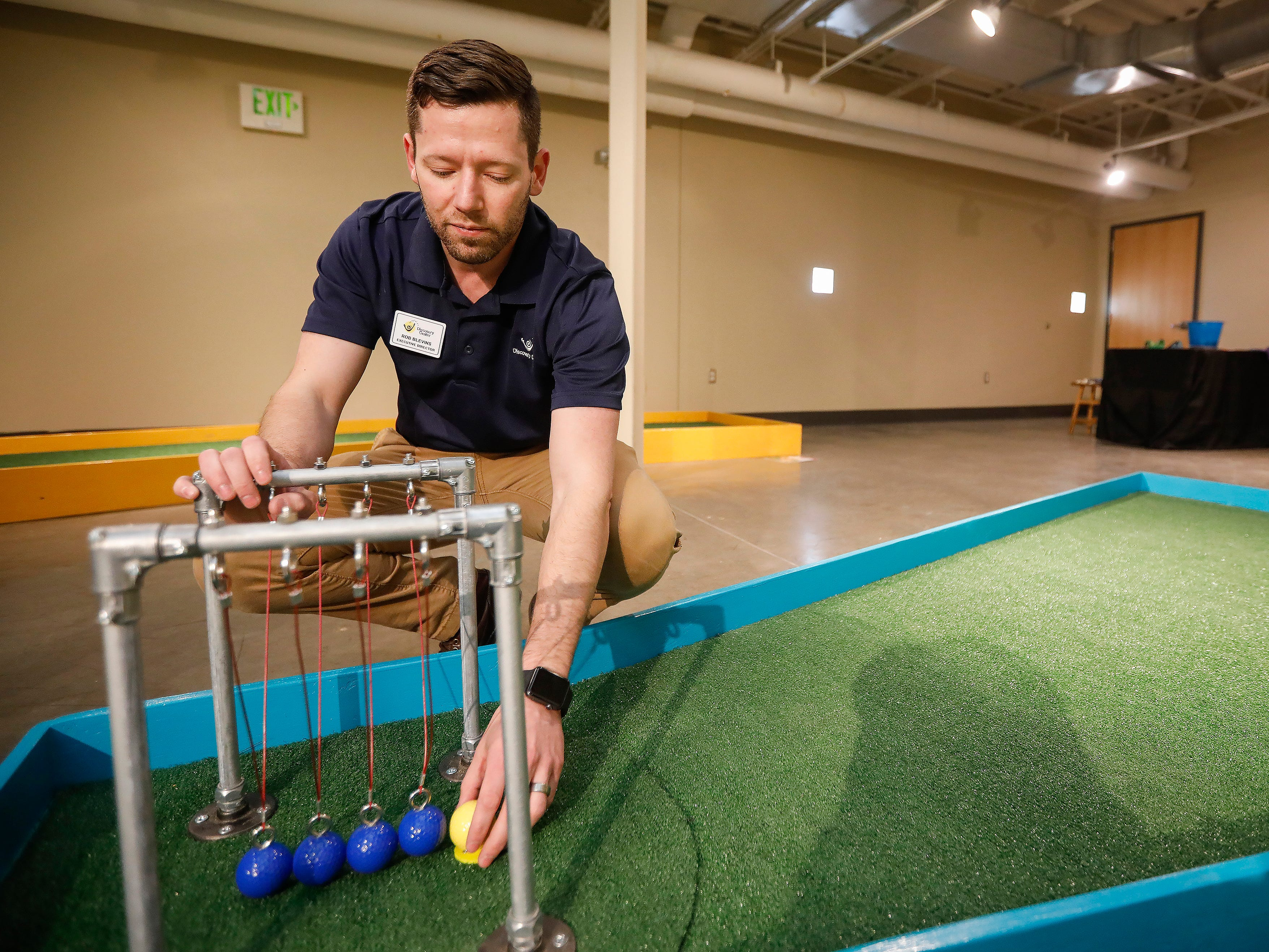 Rob Blevins, executive director at the Discovery Center, sets up the ball in front of a Newton's cradle at the new 9-hole indoor miniature golf course at the science museum. The new exhibit opens to the public on Sunday, March 31, 2019.