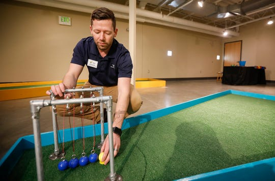 Rob Blevins, executive director at the Discovery Center, sets up the ball in front of a Newton's cradle at the new 9-hole indoor miniature golf course at the science museum. Blevins was named Emerging Leader of the Year.