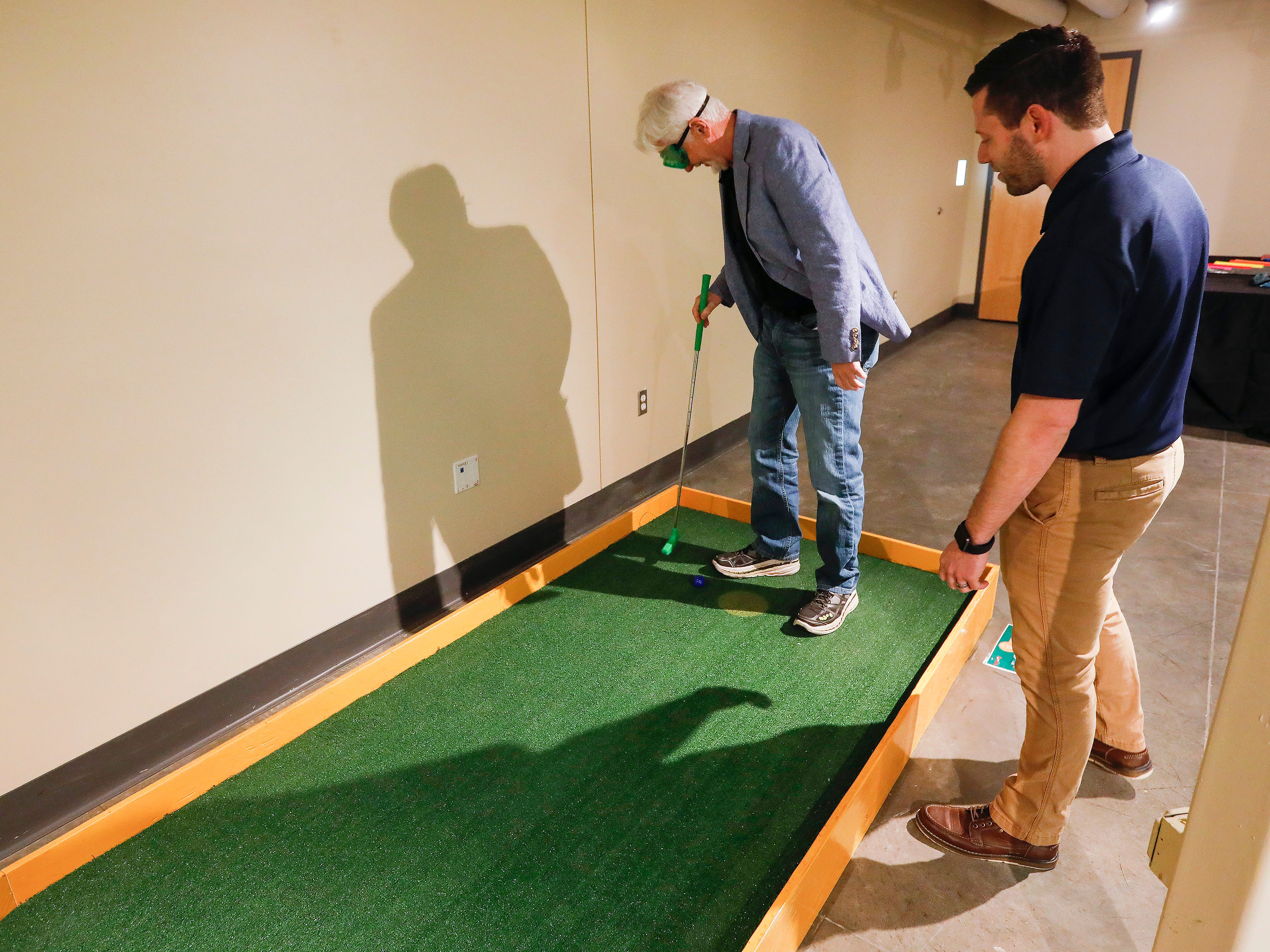 Rob Blevins, right, executive director at the Discovery Center, watches as Steve Pokin tries to line up a shot while wearing goggles at the new 9-hole indoor miniature golf course at the science museum. The new exhibit opens to the public on Sunday, March 31, 2019.