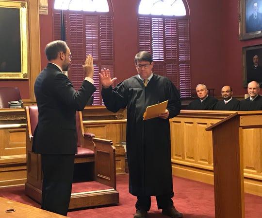 Paul A. Dryer (left) is sworn in Thursday by Judge W. Chapman Goodwin.