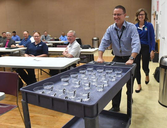 """Scott Meagher (second from right), of the City of Port St. Lucie Utilities, along with Jenny Tomes (right), utility marketing coordinator for the City of Port St. Lucie, brings in three sets of water samples for judging at the start of the water tasting contest Thursday, March 28, 2019, at the Port St. Lucie Community Center. """"It's friendly competition. We're all partners in the water treatment industry and it's really just a nice way to get together and talk about best practices and share ideas, just a friendly competition,"""" Tomes said."""