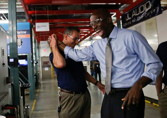 In this Wednesday, March 27, 2019,  photo, Miramar Mayor Wayne Messam, right, laughs with Stephen Turrisi, left, the director of training and technical services at JL Audio during a tour in Miramar. Messam announced March 28, 2019, he is running for the Democratic presidential nomination.