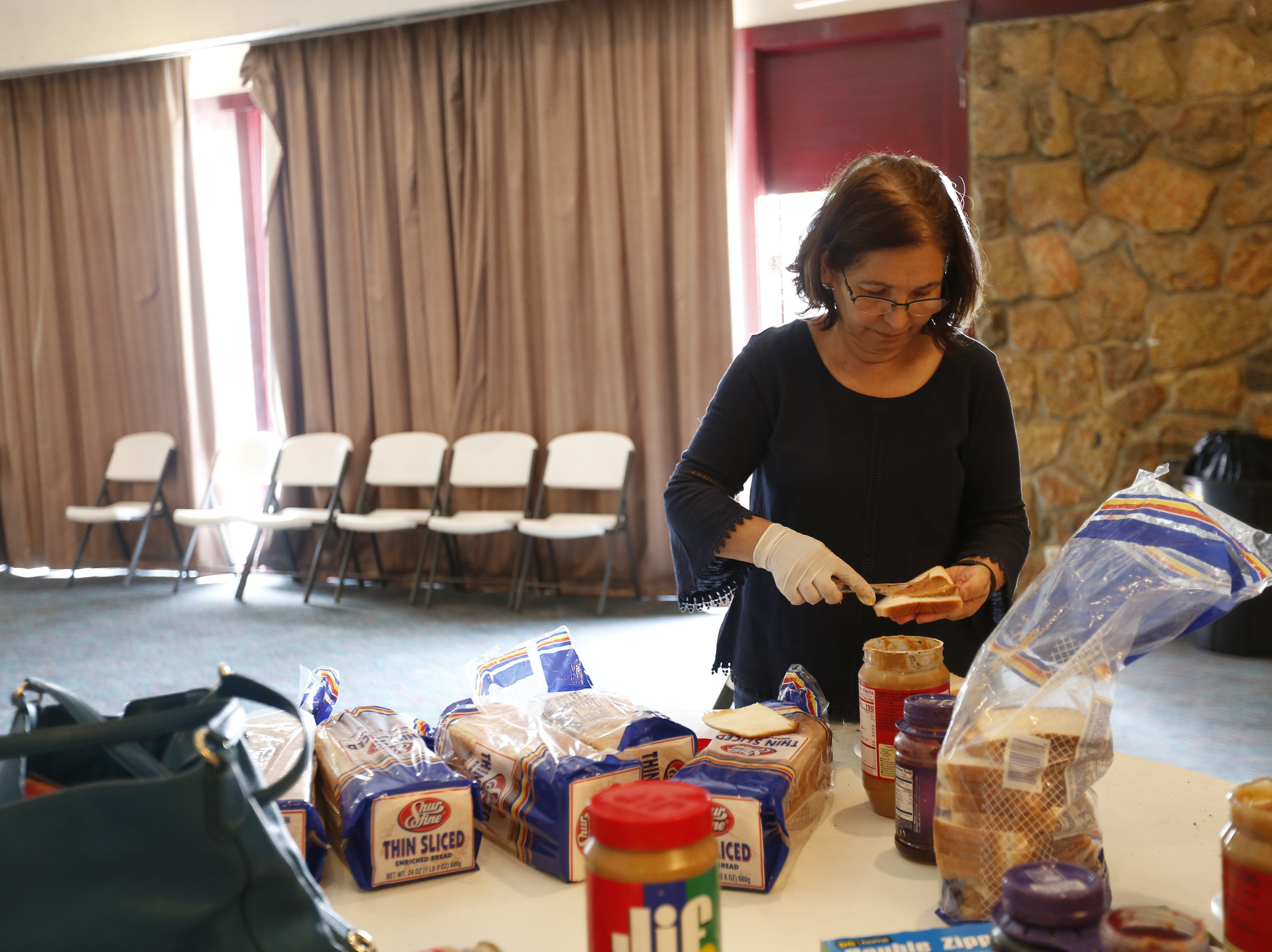 Noelia Molina, 61, helps prepare peanut butter and jelly sandwiches for migrants at a west El Paso hotel.