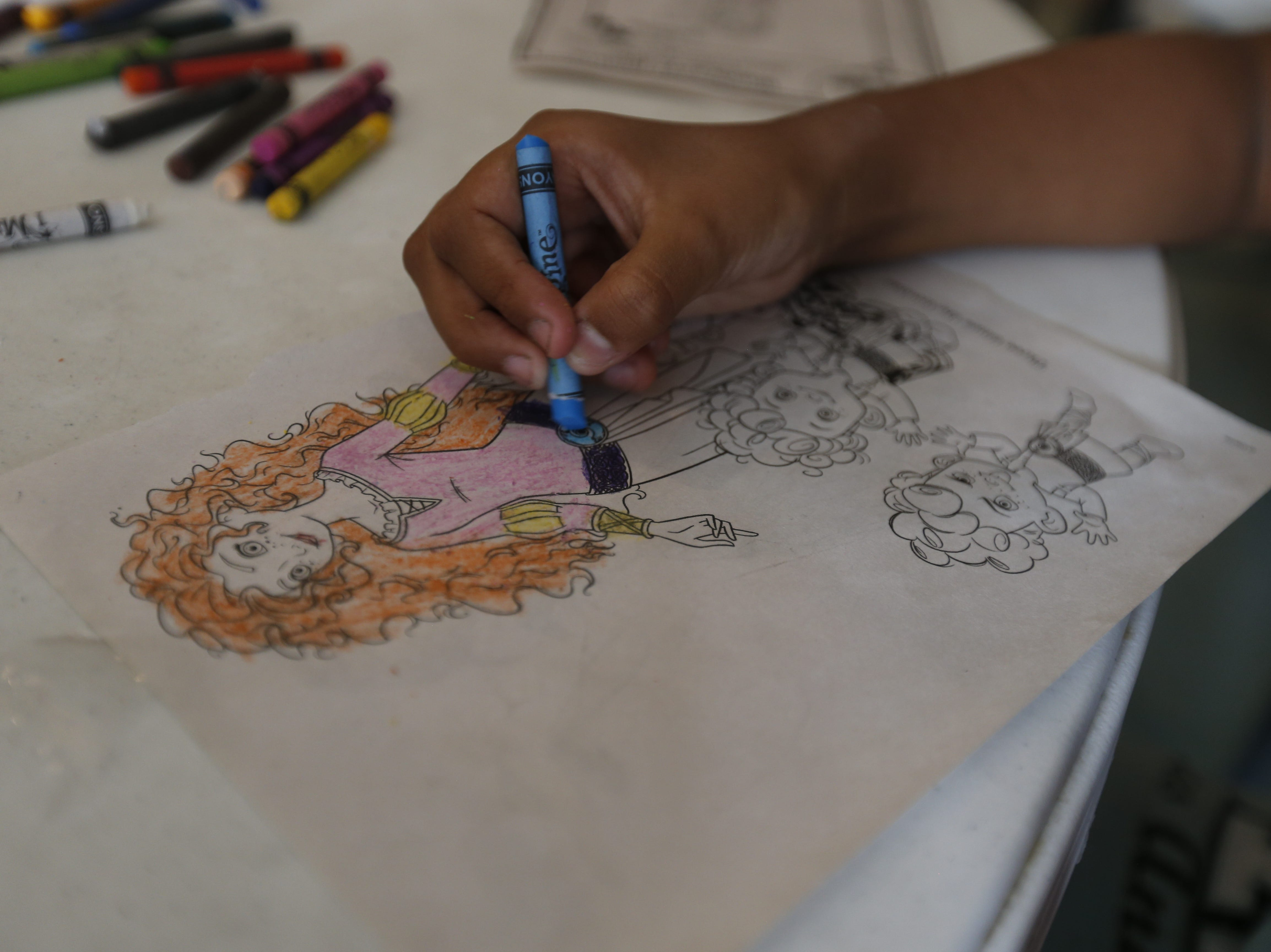 A migrant child colors in a drawing after arriving at a west El Paso hotel on Wednesday.