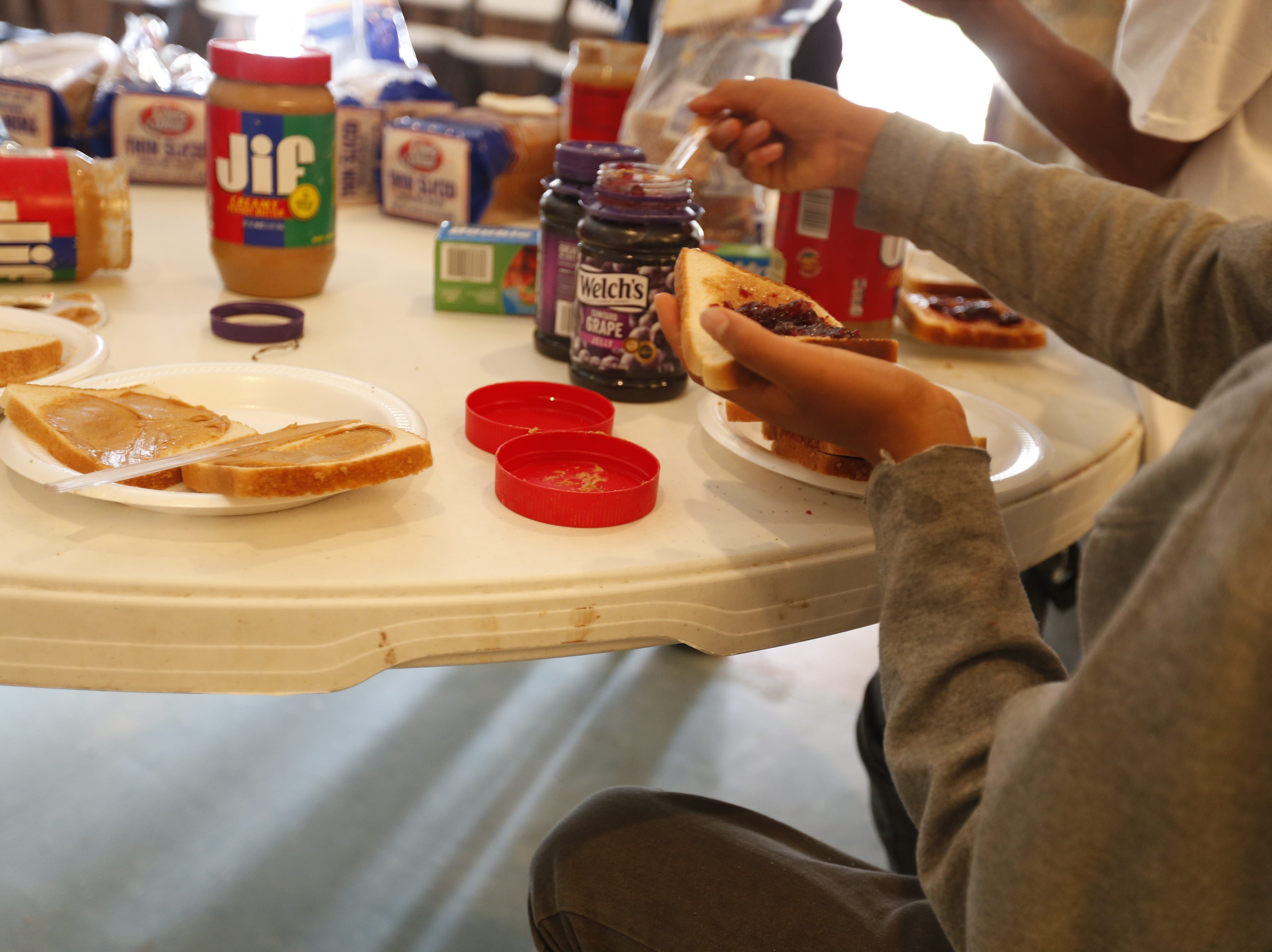 A 12-year-old boy from Mexico helps prepare peanut butter and jelly sandwiches.