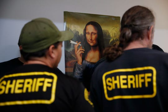In this March 15, 2018, file photo, a group of undercover Los Angeles County sheriff's deputies gather inside an illegal marijuana dispensary during a raid in Compton. Mayor Eric Garcetti said Wednesday that Los Angeles is considering a major crackdown on illegal marijuana shops that have been bedeviling the city's legal marketplace.