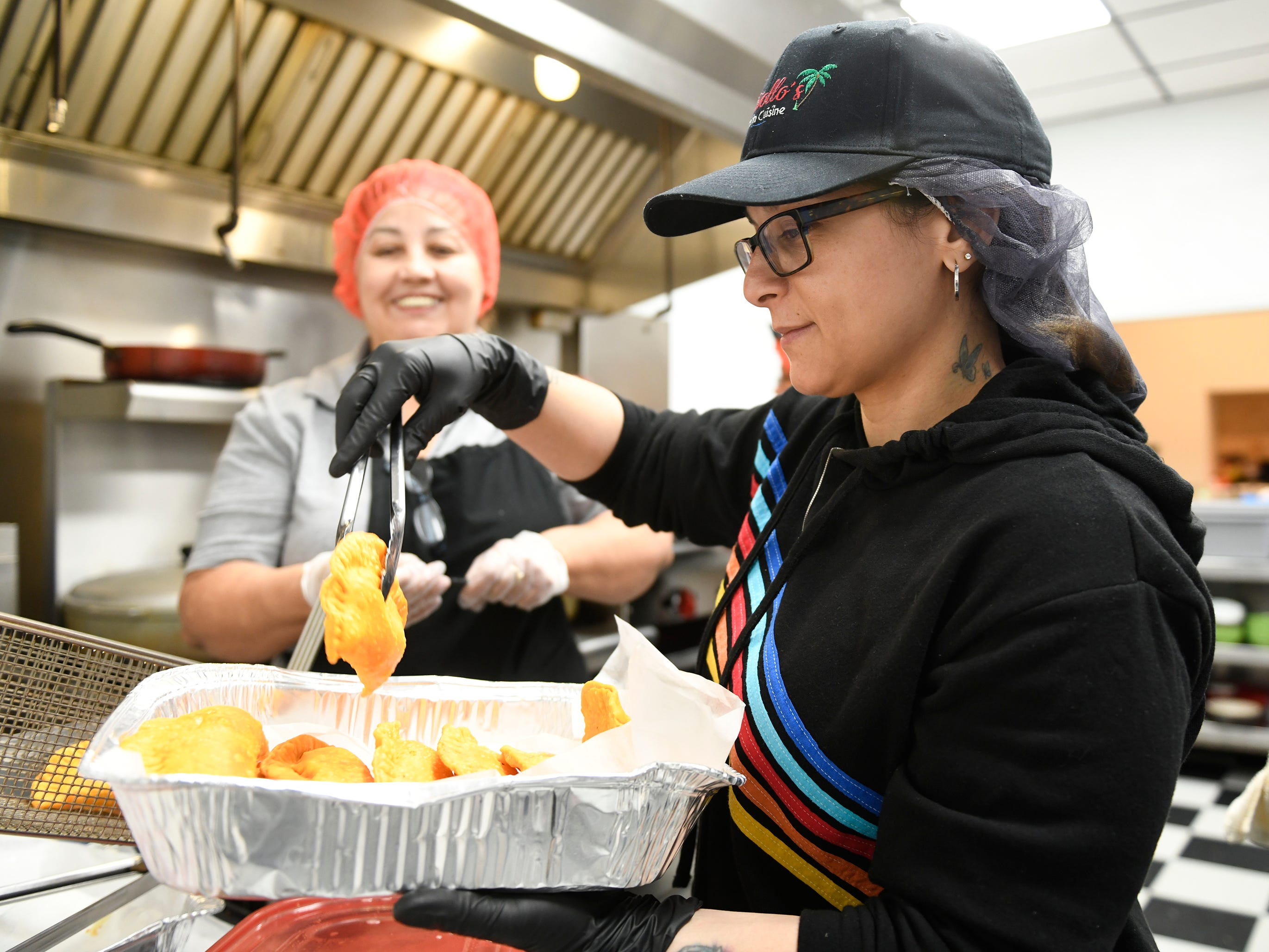 Elsie Guzman takes hot pastelillos out of the deep-fryer during the lunch time rush at Criollo's Latin Cuisine in Millville.