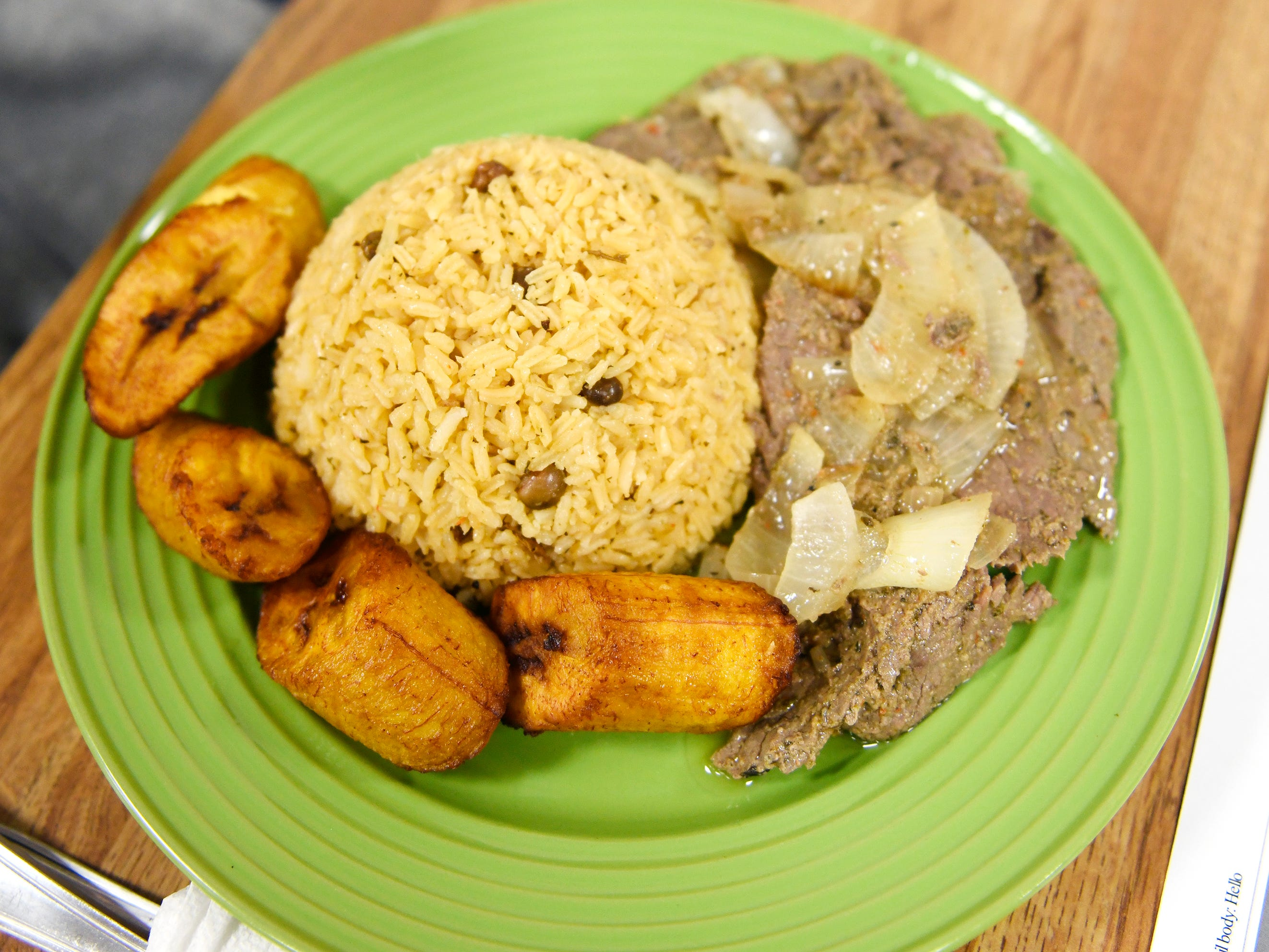 Criollo's steak and onions entree with rice and plantains pictured here on Wednesday, March 27, 2019.