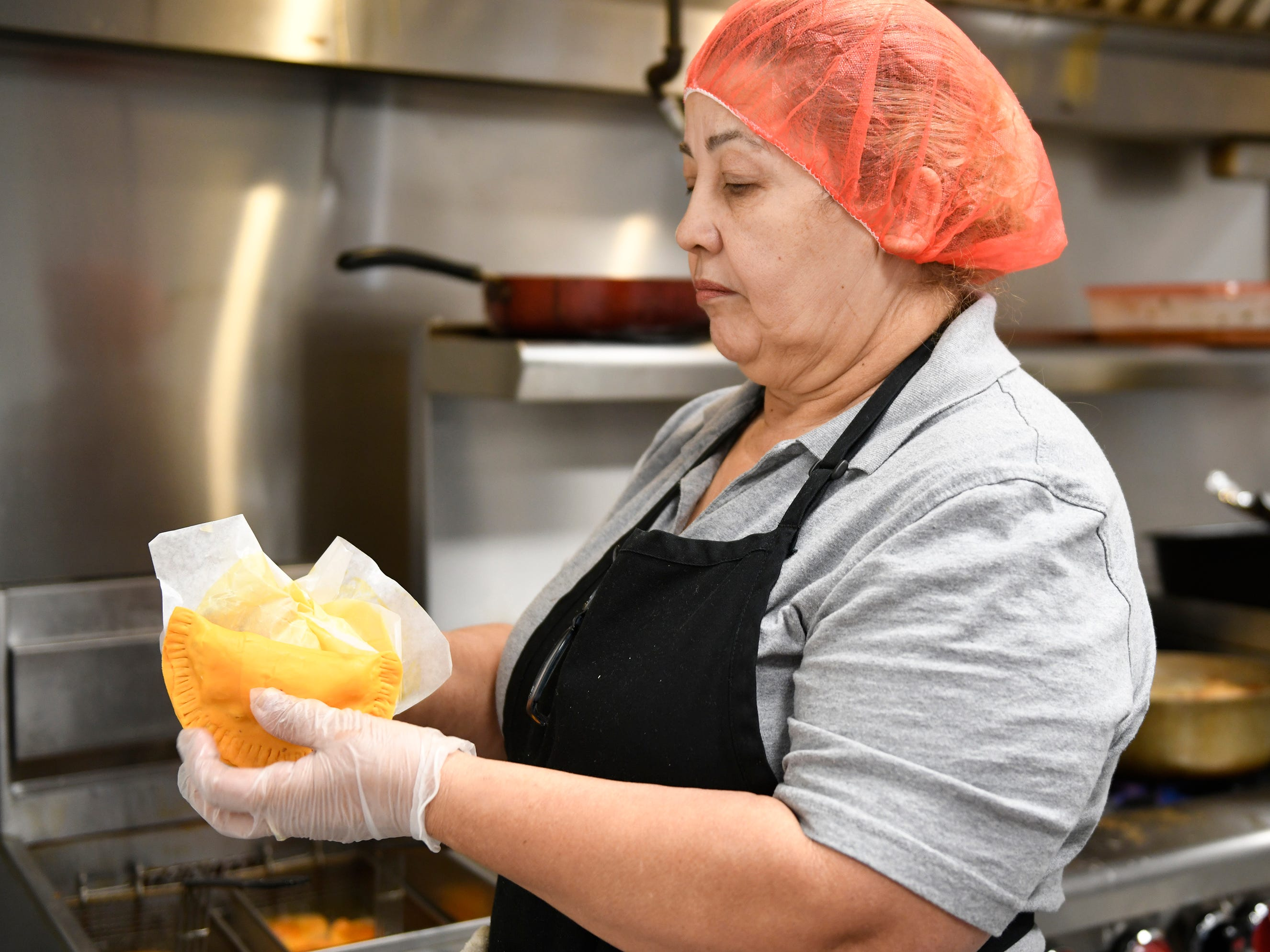 Kathy Flores holds a pastelillo that she prepared at Criollo's Latin Cuisine. The Millville restaurant specializes in Spanish, Puerto Rican and Dominican food.