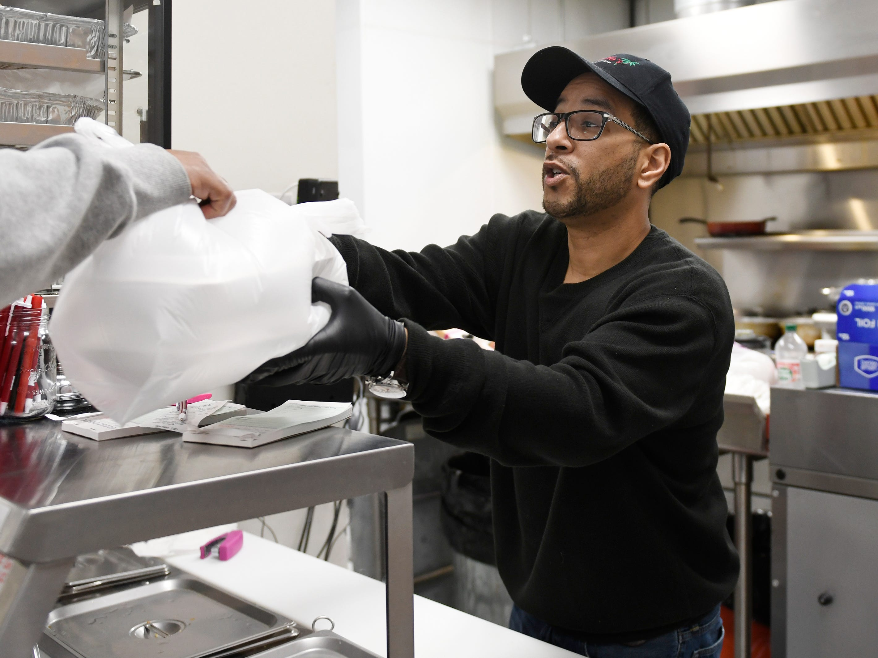 Criollo's Latin Cuisine owner Scott Guzman gives a customer their lunch order on Wednesday, March 27, 2019. The restaurant is located inside the EZ-Mart on West Main Street in Millville.