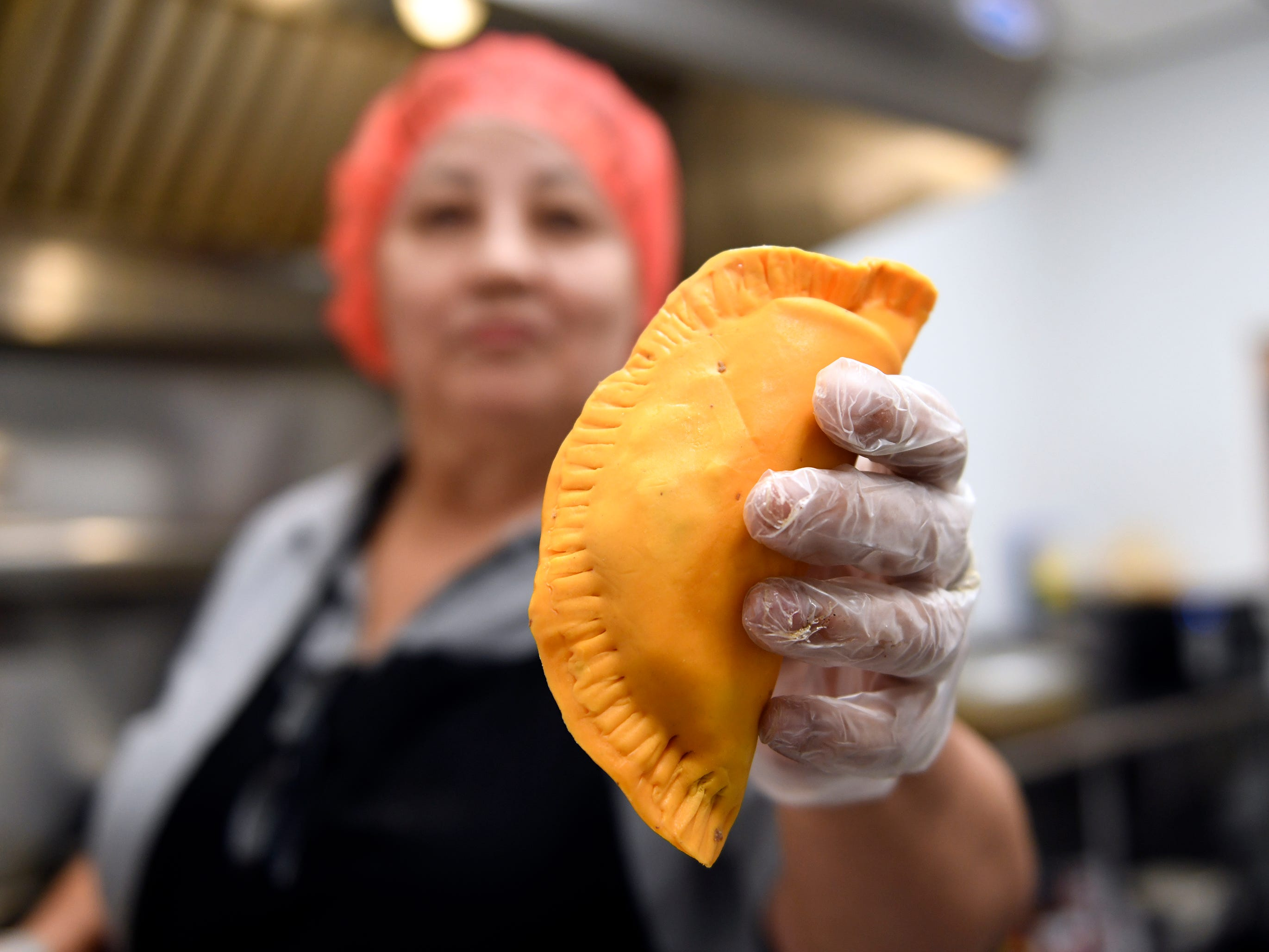 Kathy Flores holds a pastelillo that she cooked at Criollo's Latin Cuisine. The Millville restaurant specializes in Spanish, Puerto Rican and Dominican food.
