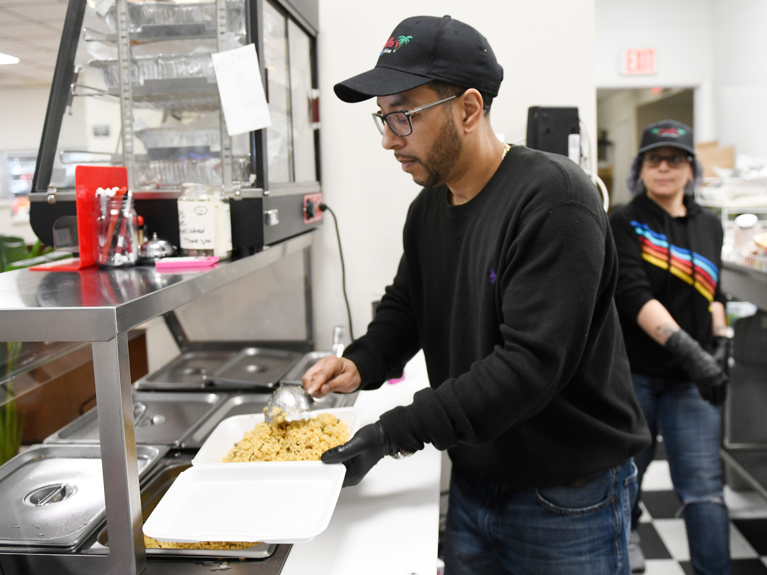 Criollo's Latin Cuisine owner Scott Guzman prepares an order for take out on Wednesday, March 27, 2019. The restaurant is located inside the EZ-Mart on West Main Street in Millville.