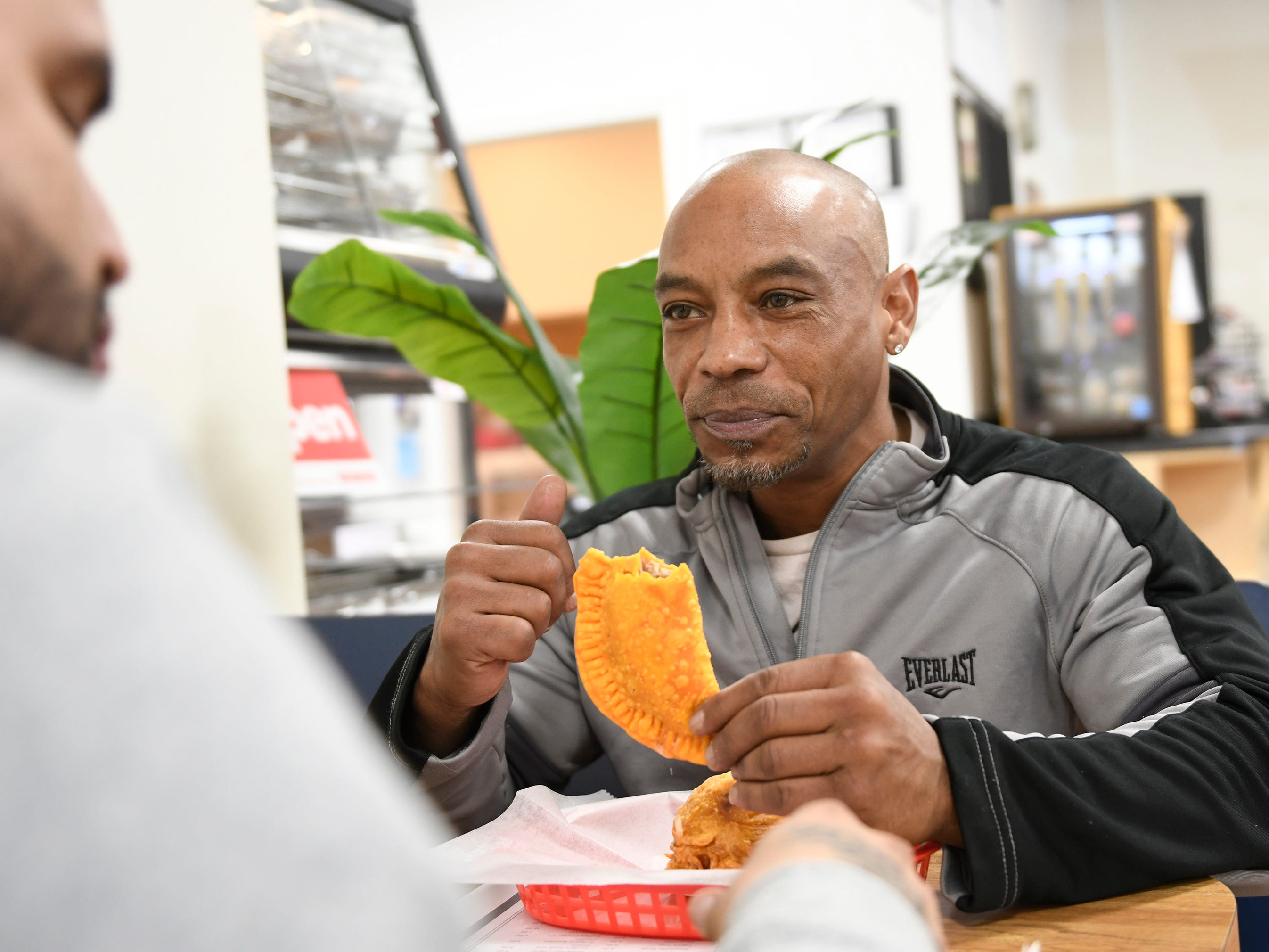 David Anthony, owner of Vila Boxing in Vineland, enjoys a pastelillo for lunch at Criollo's Latin Cuisine in Millville on Wednesday.