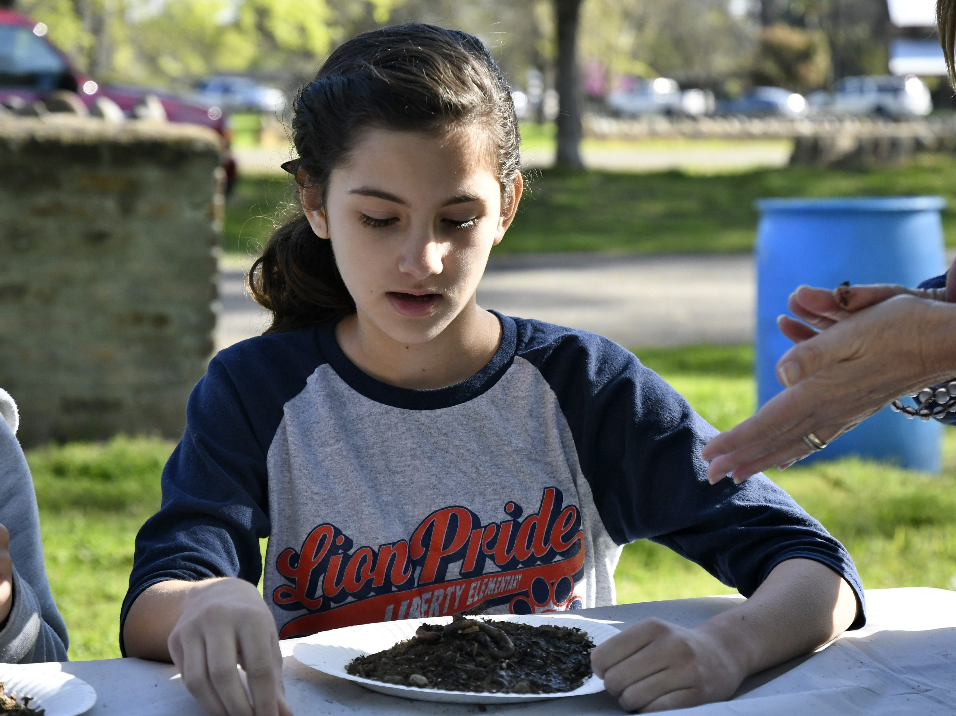 Liberty Elementary student Kira Davis looks at a worm through a magnifying glass at TCOE's Arbor Day celebration at Mooney Grove Park on Thursday, March 28, 2019.