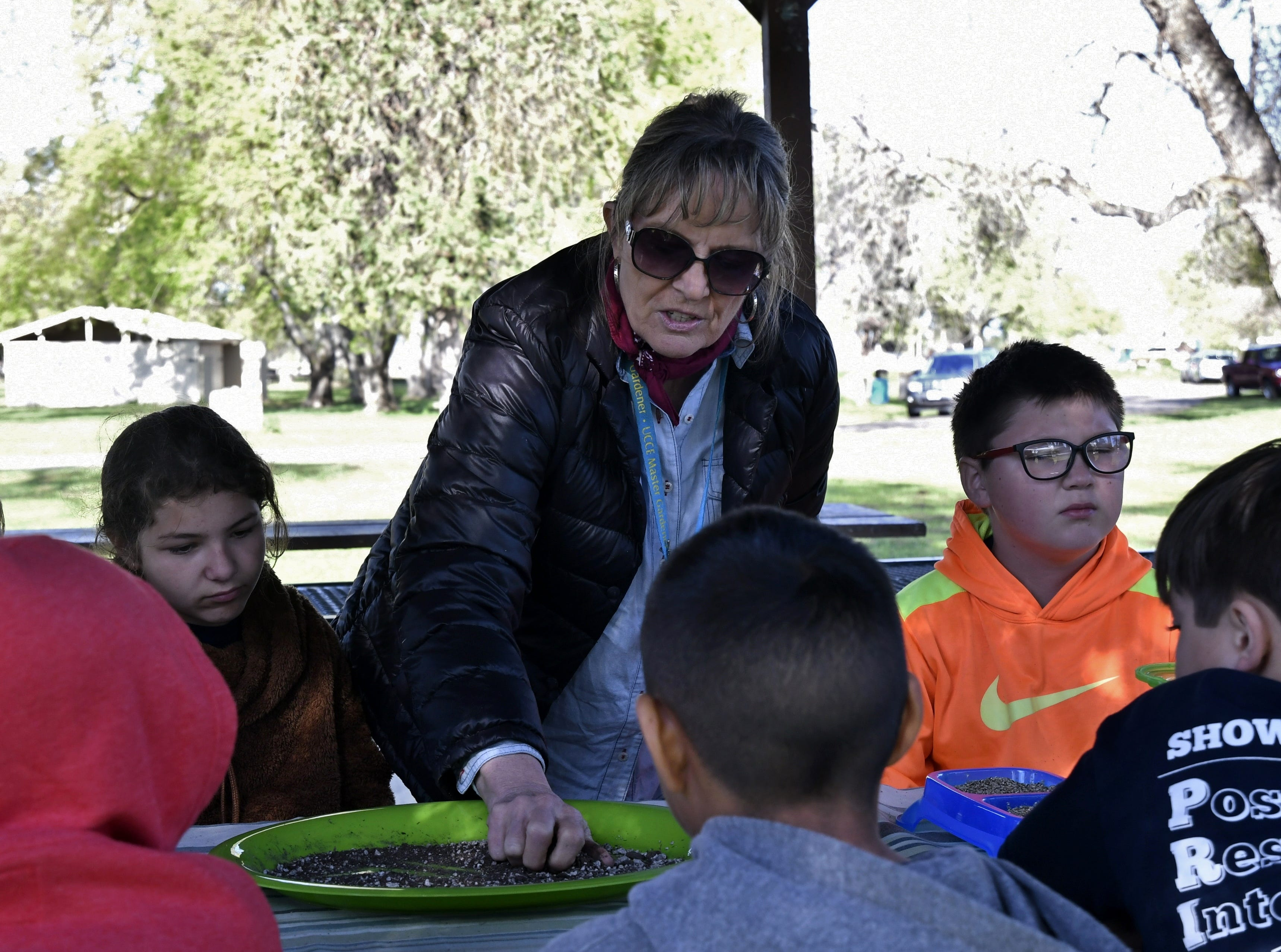 Barb Johnson, you outreach director with University of California's Master Gardeners, shows Liberty Elementary students how to make seed bombs at Mooney Grove Park on Thursday, March 28, 2019.
