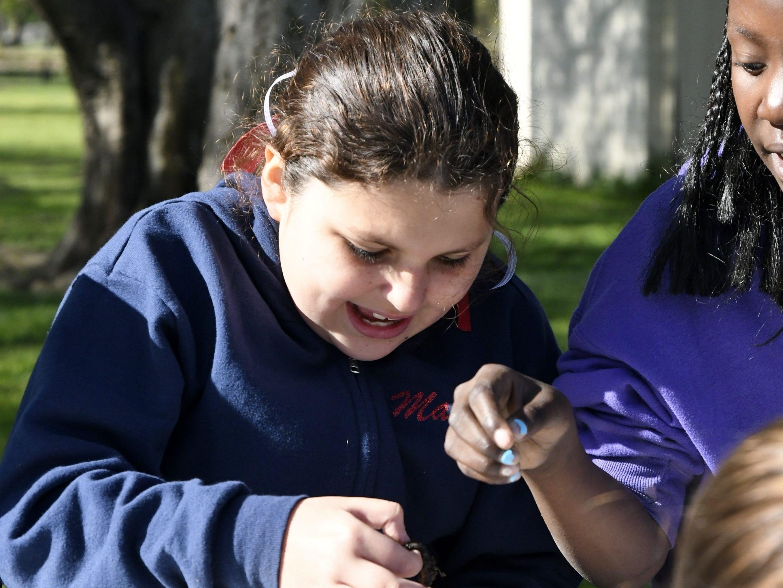 Maria Mayorga, 9, holds a worm at TCOE's Arbor Day celebration at Mooney Grove Park on Thursday, March 28, 2019.