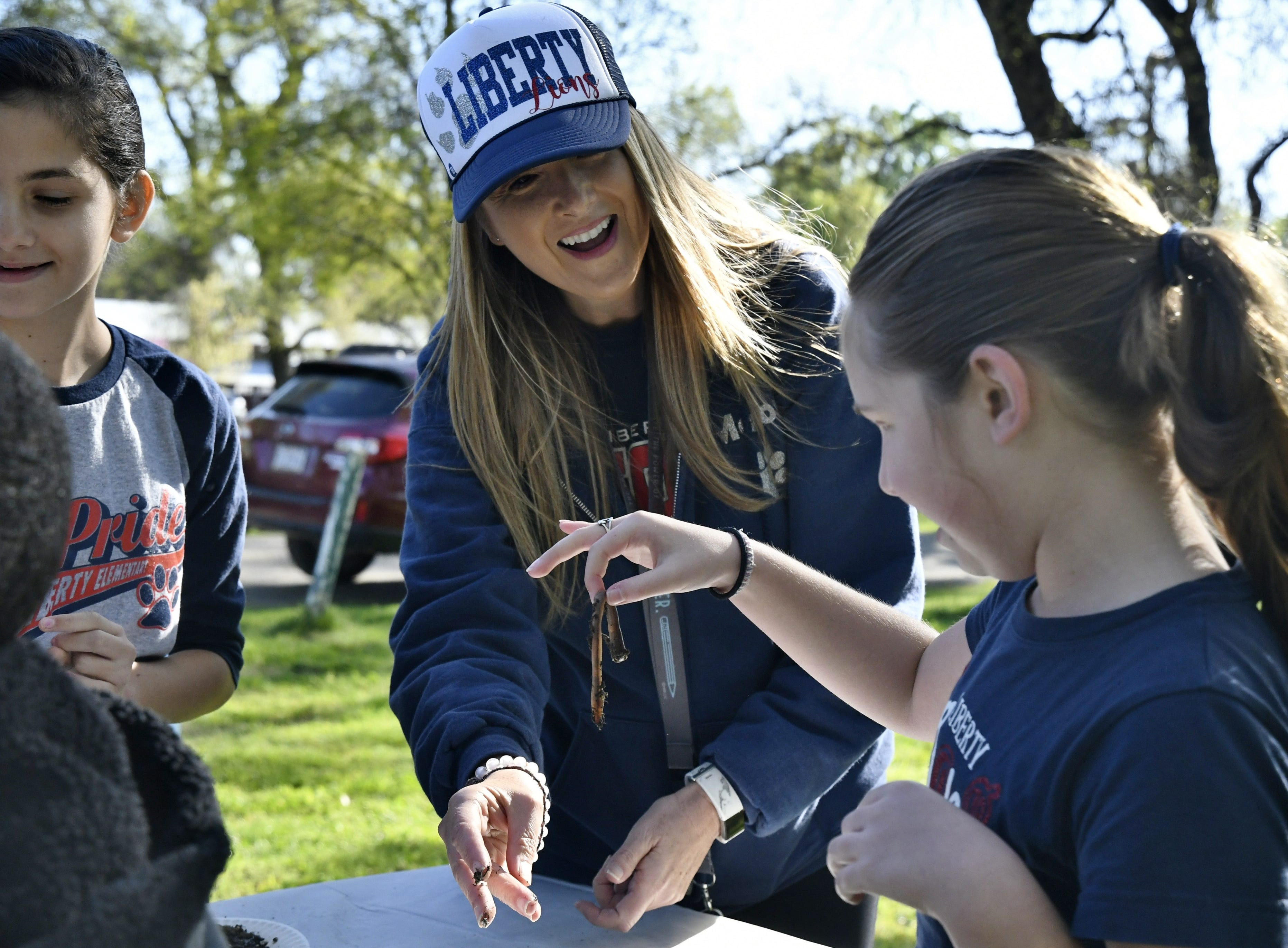Liberty Elementary teacher Brandle Mason helps student Sophie Huard hold a worm at TCOE's Arbor Day celebration at Mooney Grove Park on Thursday, March 28, 2019.