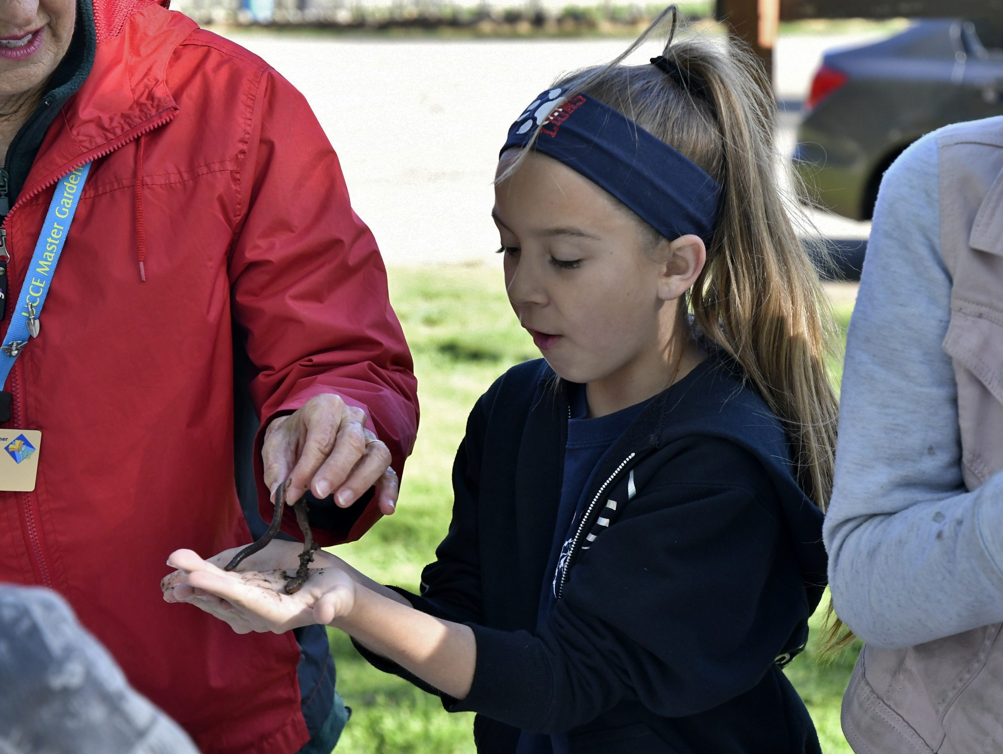 Liberty Elementary student Marissa Marroquin holds a worm at TCOE's Arbor Day celebration at Mooney Grove Park on Thursday, March 28, 2019.