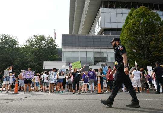 FILE - In this Aug. 17, 2018, file photo, family and friends who have lost loved ones to OxyContin and opioid overdoses protest outside the headquarters of Purdue Pharma, which is owned by the Sackler family, in Stamford, Conn. The Sackler family came under scrutiny when a legal filing in Massachusetts gave detailed allegations of how family members and other Purdue Pharma executives sought to push prescriptions for the drug OxyContin and downplay its addiction risks. (AP Photo/Jessica Hill, File)