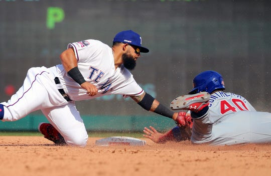 Texas Rangers second baseman Rougned Odor (12) tags out Chicago Cubs Willson Contreras (40) on a steal attempt during the fifth inning of a baseball game Thursday, March 28, 2019 in Arlington, Texas. (AP Photo/Richard W. Rodriguez)