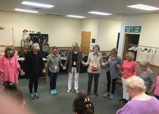 Members of the Faith Refuge Fashion Boutique steering committee gather for  a prayer circle before opening the doors to the fundraiser's inaugural event in 2018.