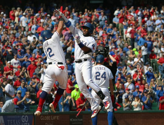 Texas Rangers' Rougned Odor (12) celebrates the home run by Elvis Andrus (1) against the Chicago Cubs in the third inning of a baseball game Thursday, March 28, 2019 in Arlington, Texas. (AP Photo/ Richard W. Rodriguez)