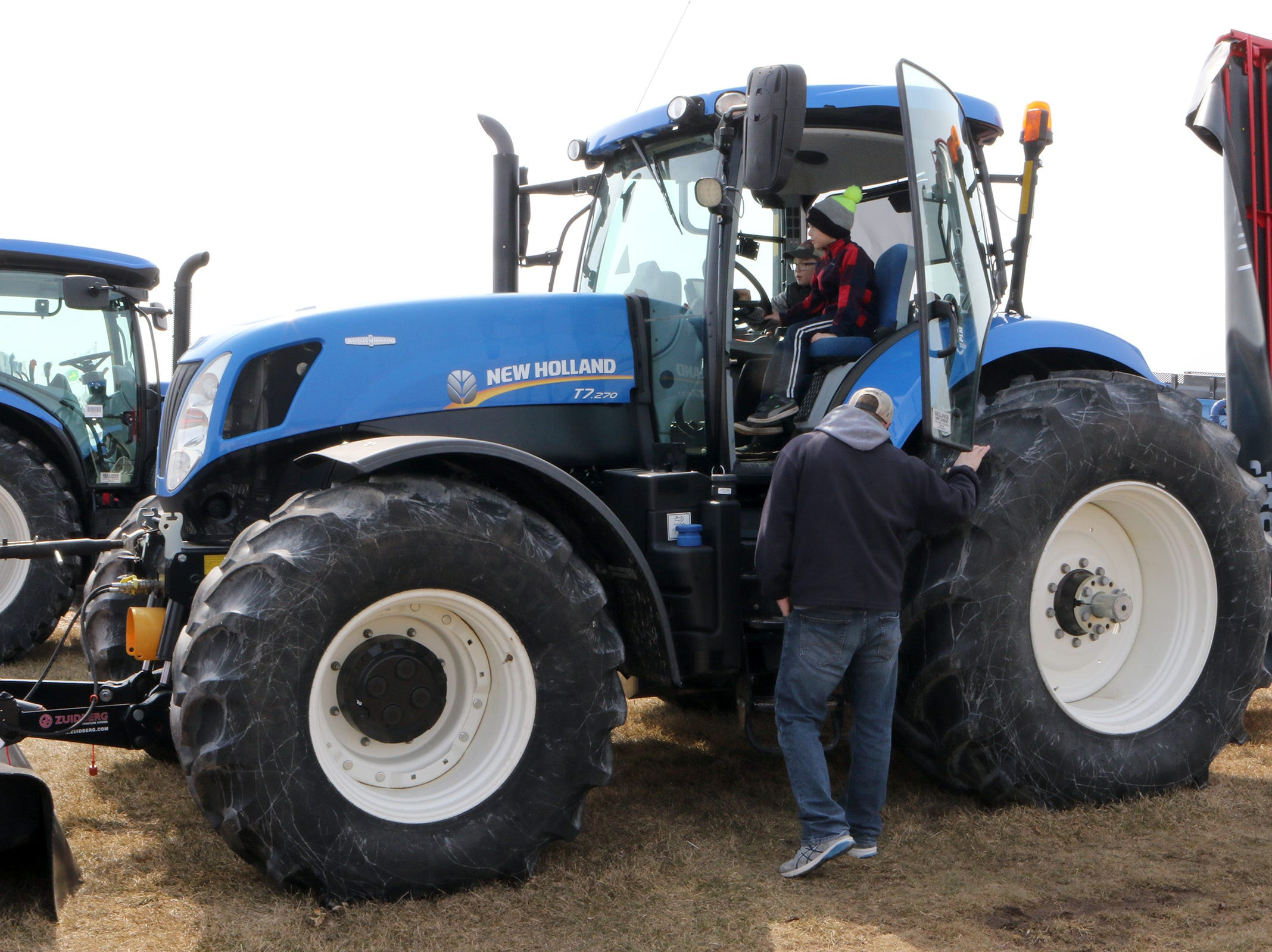 Bryan Schultz, of Oshkosh, and his sons Owen, 12 (left) and Evan, 8, check out a New Holland mower at the Wisconsin Public Service Farm Show on March 27 in Oshkosh.