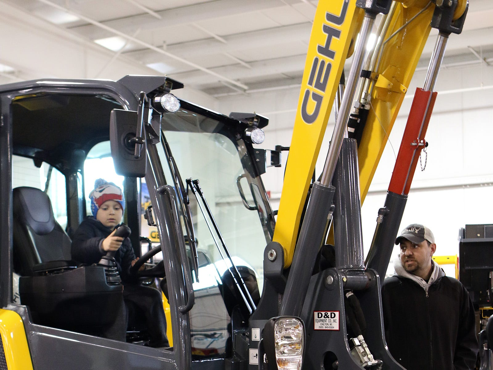 Emmet Zodrow, 6, of Green Lake, checks out the controls on a Gehl tractor while dad, John looks over the outside during the Wisconsin Public Service Farm Show on March 27 in Oshkosh.