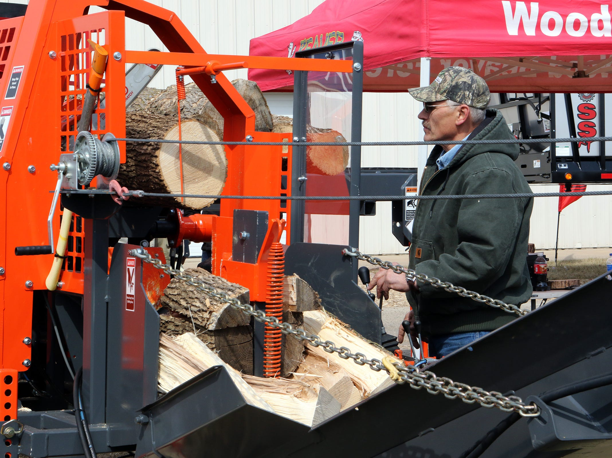 Dave Faytik, with Multitek, demonstrates how a firewood processor makes easy work of cutting and splitting wood during the Wisconsin Public Service Farm Show on March 27 in Oshkosh.