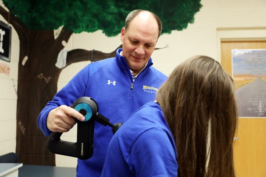 Maysville High School athletic trainer Joe Johnson helps sprinter Paige Webb get ready for track practice. Johnson was named the Athletic Trainer of the Yearby the Ohio Athletic Trainers' Association.