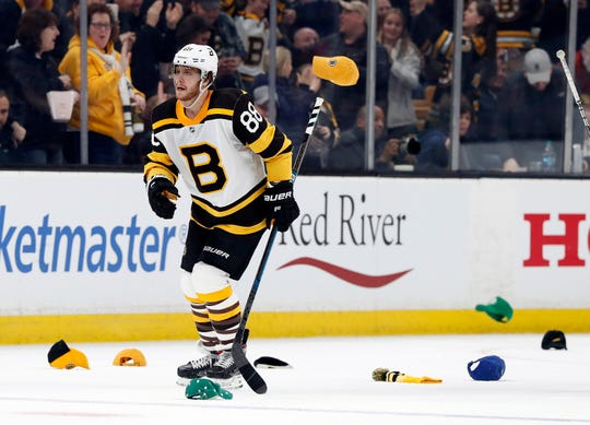 Hats litter the ice as Boston Bruins right wing David Pastrnak scores his third goal on his way to a five-point night.