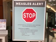 In this Jan. 30, 2019, file photo, a sign posted at The Vancouver Clinic in Vancouver, Wash., warns patients and visitors of a measles outbreak.