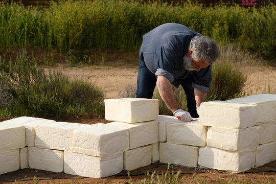 Cosimo Cavallaro isbuilding a 6-foot high, 3-foot wide wall made of expired cheese blocks, a Facebook page for the artistic project says.