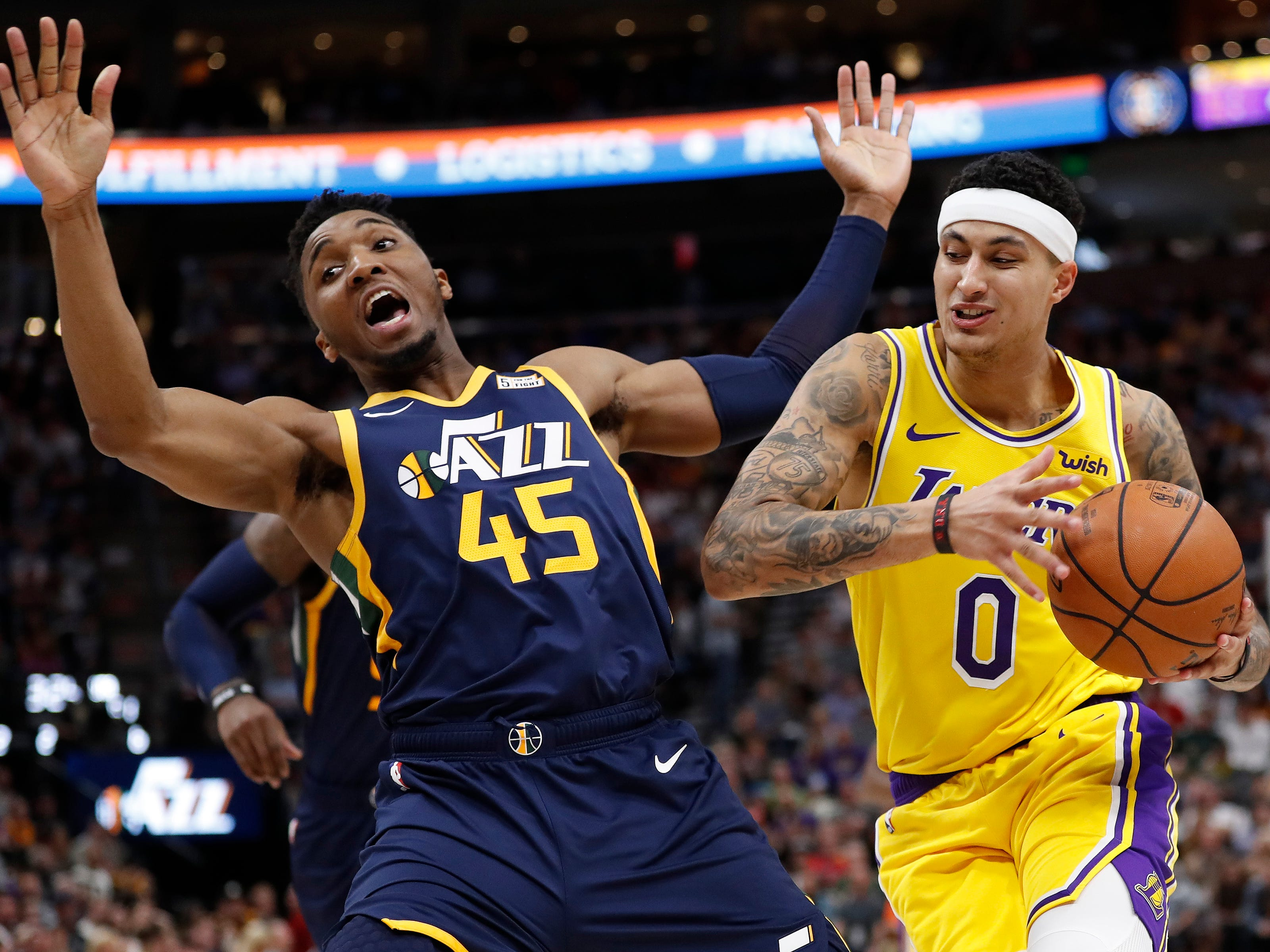 March 27: Utah Jazz guard Donovan Mitchell (45) takes a hit from Los Angeles Lakers forward Kyle Kuzma (0) in the second quarter at Vivint Smart Home Arena.
