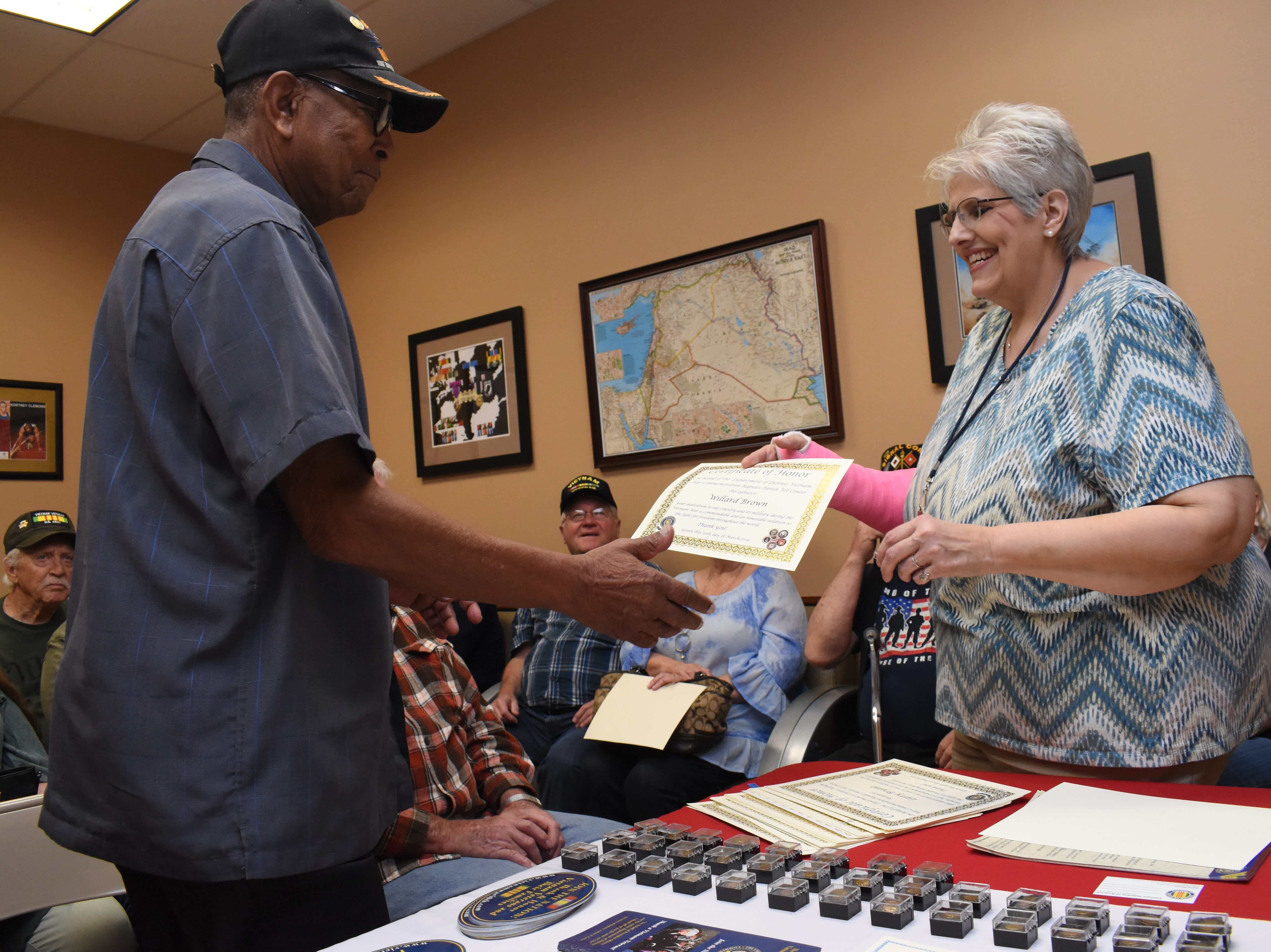 """Elizabeth Cheryl Nolen (right) executive director of the Rapides Parish Vet Center, hands Willard Brown, a Vietnam War veteran, a certificate and pin in honor of his service during the Vietnam War. The Rapides Parish Vet Center, located at 5803 Coliseum Blvd., which serves combat-era military veterans, held a pin ceremony Friday, March 29, 2019 for Vietnam War veterans in recognition of Vietnam Veterans Day. Over the course of the day over 50 pins and certificates were handed out. Vietnam Veterans Day honors those who served and their families. The Vietnam War Veterans Recognition Act  was signed into law in 2017. """"Welcome Home Vietnam Veterans Day"""" is celebrated in most states on March 29 or March 30. On March 29, 1973 the last troops withdrew from Vietnam and American prisoners of war were returned. This is also the date President Richard Nixon designated for the first Vietnam Veterans Day in 1974. For more information about the Rapides Parish Vet Center and their services, call (318) 466-4327."""