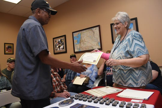 """Elizabeth Cheryl Nolen (right) executive director of the Rapides Parish Vet Center, hands Willard Brown, a Vietnam War veteran, a certificate and pin in honor of his service during the Vietnam War. The Rapides Parish Vet Center will host a """"Rocks for Remembrance Walk"""" Saturday, May 18, 2019 at Camp Beauregard."""