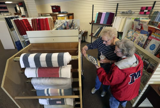 Kathy Eisenschink, left, and Linda Pristelski check out new products at Fox Cities Quilt Co., in Appleton. Both women are from Green Bay.
