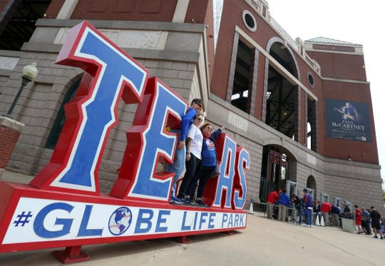 Cubs fans pose for a photo outside of Globe Life Park before the opening day baseball game between the Chicago Cubs and Texas Rangers Thursday, March 28, 2019 in Arlington, Texas. (AP Photo/Richard W. Rodriguez)