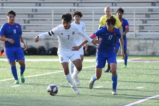 Abilene High's Joseph Martinez (7) holds off an Arlington Bowie defender during the Region I-6A bi-district playoff at Granbury's Pirate Stadium on Thursday, March 28, 2019.