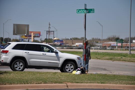 A man solicits donations while standing at Catclaw Drive and South Clack Street on Friday.